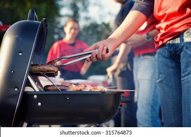 Tailgating: Man Grilling Sausages And Other Food For Tailgate Party