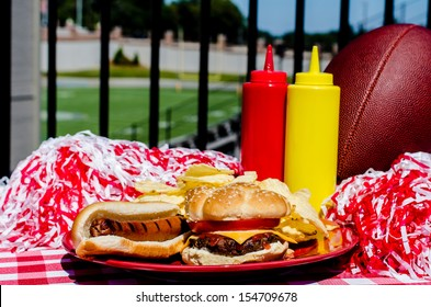 Tailgating party with cheeseburger, hot dog, potato chips, pom poms, and football.  Football field in background.