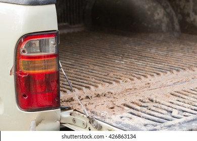 Taillights and tailgate of a pickup truck dirty.