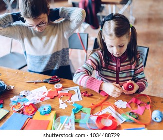 tailor art workshops for children - a girl sewing felt decorations - colorful fabrics lying on a table