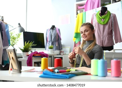 Tailor Creating Clothes Handicraft Sewing Concept. Young Needlewoman or Dressmaker Sitting at Working Table. Caucasian Woman Suit Designer. Fabric, Sewing Tools and Spools of Color Thread on Desk