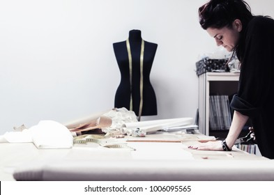 tailor cuts scissors, tailoring materials, professional female tailor using scissors and draft design cardboard on cloth material cut clothing design samples in production studio pattern table.