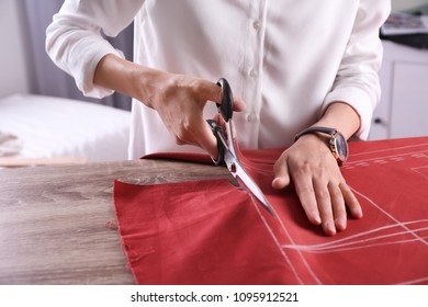 Tailor cutting fabric at table in atelier, closeup
