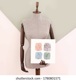 A tailor dummy with wooden parts holding an acrylic painting of some little plant doodles front view fashion and design concept image on green and white background