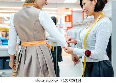 Tailor fitting a bespoke dress to a woman customer with measure tape around her neck