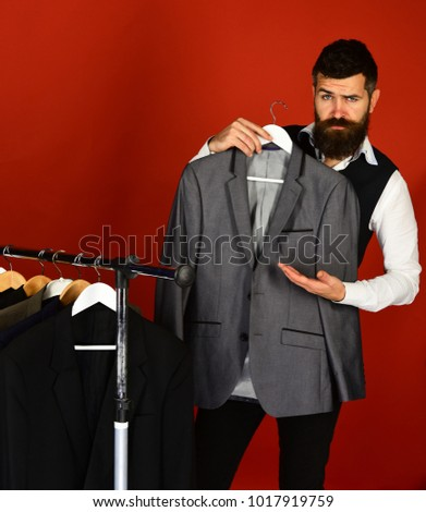 828925aba04 Tailor with flirty face holds grey suit near custom jackets on red  background. Designer presents
