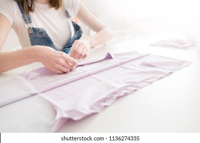 tailor girl cuts cloth with scissors. sewing business