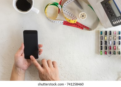 tailor hands pressing phone on rough work table