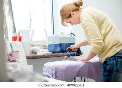 Tailor ironing the fabric. seamstress irons dress in a sewing workshop