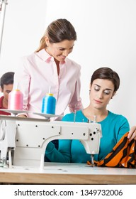 Tailor Looking At Colleague Stitching In Factory