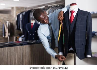 Tailor makes measurements of a business suit