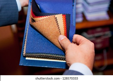 tailor. Man searching through fabrics for a suit