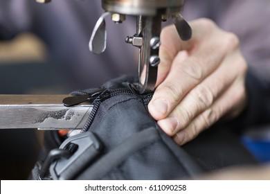 Tailor man sews up a bag in a workshop