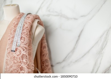 Tailor mannequin with coral lace fabric and tape measure alongside marble wall. Luxury floral designed lace fabrics for sewing wedding dress, lingerie and bridesmaid dresses. Cotton silk blend fabric.