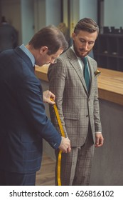 Tailor measures a man in studio