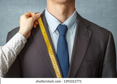 The tailor measures the suit with a measuring tape close-up