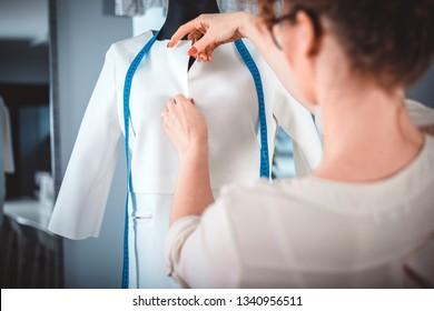 Tailor measuring lady jacket on mannequin at fashion design workshop