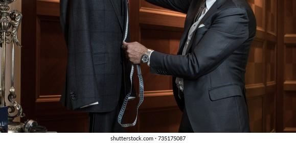 Tailor measuring suit on dummy