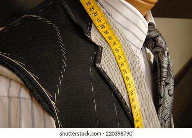 Tailor shop mannequin with measuring tape across neck.