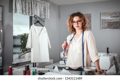 Tailor shop owner posing over sewing work desk, craftswoman in fashion workshop