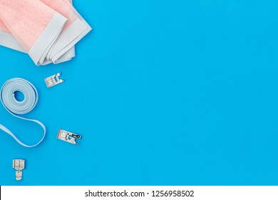 Tailor shop with thread, fabric. Sewing as hobby. Blue background top view mockup