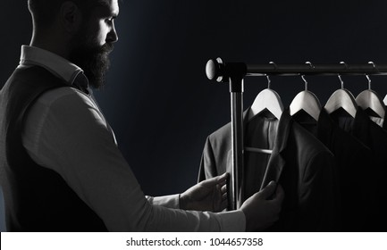Tailor, tailoring. Men's suit, tailor in his workshop. Elegant man's suits hanging in a row. Luxury mens classic suits on rack in elegant men's boutique. Black and white
