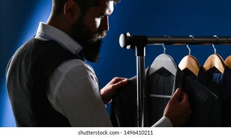 Tailor, tailoring. Men's suit, tailor in his workshop. Elegant man's suits hanging in a row. Luxury mens classic suits on rack in elegant men's boutique.