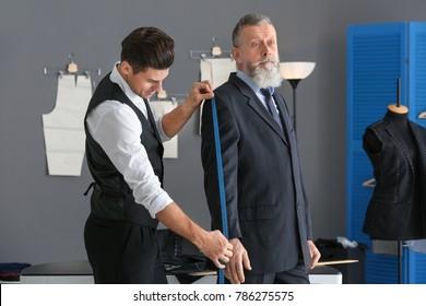 Tailor taking client's measurements in atelier