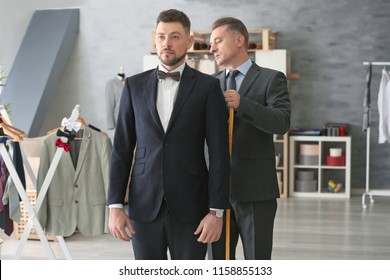 Tailor taking man's measurements in atelier