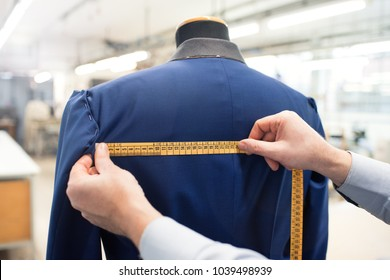 Tailor using measuring tape while doing jacket measurement in workshop