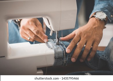 Tailor working with blue denim jeans. Tailor hem the blue jeans. - Shutterstock ID 1435795466