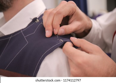 Tailor working on custom made suit in atelier, closeup