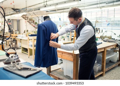 Tailor working on a partially completed new blue jacket on a mannequin in his large spacious workshop tucking in the pleats at the back with his hands as he shapes the fabric