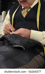 Tailor working at studio with pattern cuttings focused on hands - a series of TAILOR related images