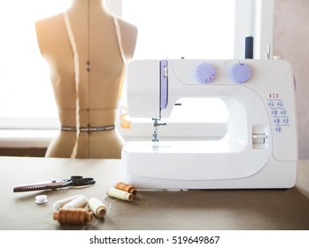 tailor workshop with white sewing machine, fashion dummy, details and cloth.
