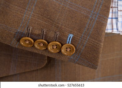 Tailored brown checked suit sleeve with buttons and checked shirt close up