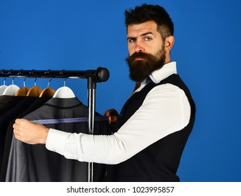 Tailoring and design concept. Man with beard by clothes rack. Tailor with confident face holds measuring tape near custom jackets on blue background. Designer takes measures near clothes hangers.