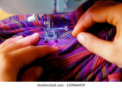Tailoring Process - Women's hands behind her sewing. purple fabric.