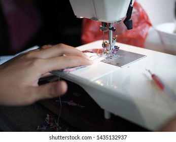 Tailoring Process - Women's hands behind her sewing machine, Work by the light of the built-in hardware lamp. Steel needle with looper and presser foot close-up.