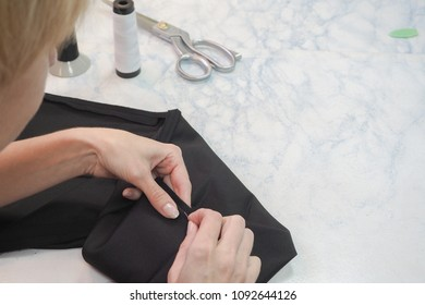 Tailor's business. The hem of the pants manually with a needle and thread