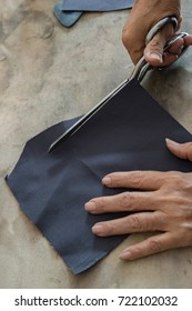 Tailor's hand cutting cloths with scissors, selective focus
