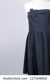 A Tailors Mannequin dressed in a Black Dress with Flower