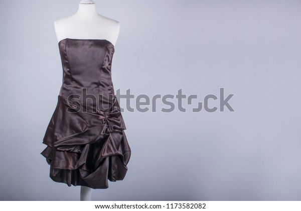 A Tailors Mannequin dressed in a Brown Satin Dress