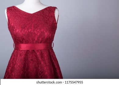 A Tailors Mannequin dressed in a Red Floral Netted Dress