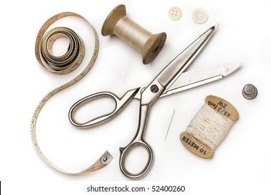 tailor's tools - scissors, measuring tape, thimble, etc. - on white