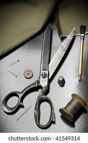 tailor's tools - scissors, needles, spool of thread and chalk pencil