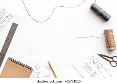 Tailor's work desk. Pattern of clothing and tools on white background top view copyspace