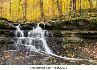 Tailwater Falls, a beautiful little waterfall in Owen County,  Indiana's Lieber State Recreation Area, cascades through a colorful autumn landscape.