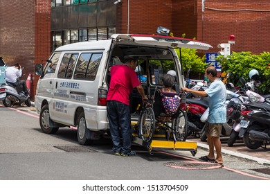 Tainan, Taiwan - 20 June 2019: An old woman in a wheelchair is lifted into a van