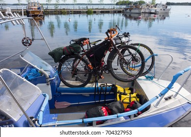 TAIPALSAARI, FINLAND - JULY 2, 2015: Touring bikes tied to a fishing boat with colorful panniers on the boat floor by lake Saimaa, Finland for crossing to the other side of the lake from Taipalsaari.